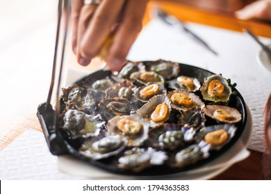 """Grilled limpets on a pan - traditional food from Madeira - """"lapas"""" in Portuguese"""