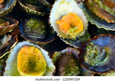 Grilled limpets served with lemon. Lapas grelhadas as a background. Traditional dish of Madeira island, Portugal and a typical snack of the Canary Islands.Seafood concept. Selective focus.