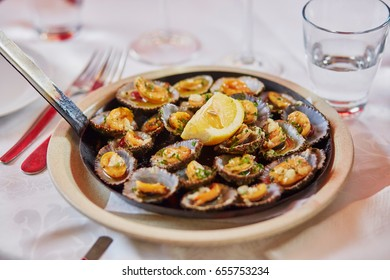 Grilled limpets served with lemon - traditional seafood on Madeira island, Portugal. Selective focus.