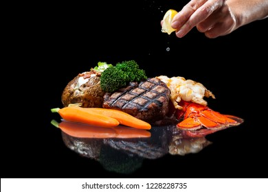 grilled lobster and filet mignon served with a loaded baked potato and vegetables isolated on a black background