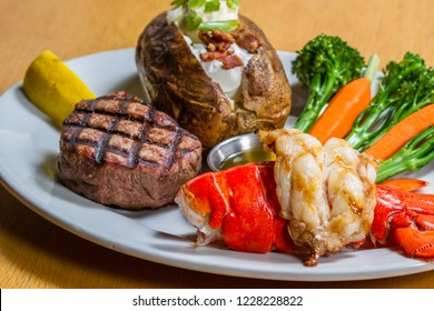 grilled lobster and filet mignon served with a loaded baked potato and vegetables