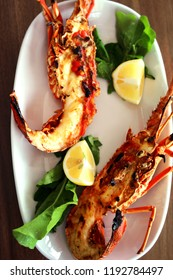 Grilled lobster on a plate with lemon and rukkola.
