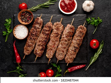 grilled Lula kebab on skewers with spices on a stone background
