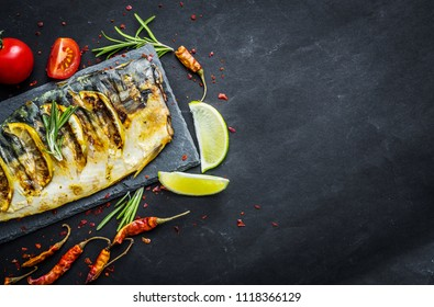 Grilled mackerel fillets with lime on black slate board, fish with vegetables