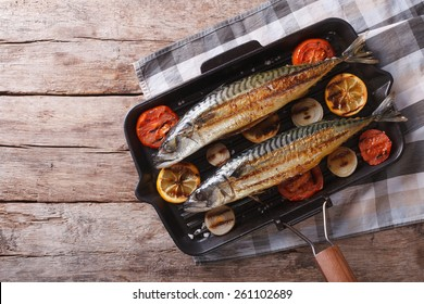 Grilled mackerel fish in a pan with vegetables. horizontal view from above