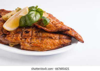 Grilled mackerel with lemon on a white