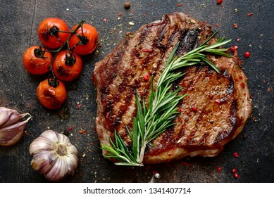 Grilled marbled beef steak with vegetables on a dark slate, stone or concrete background.Top view with copy space.