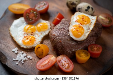 Grilled marbled beefsteak with fried quail eggs and cherry tomatoes, close-up, selective focus