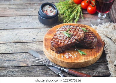Grilled marbled meat steak Filet Mignon with seasonings. Juicy beef steak on cutting board.