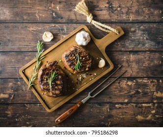 Grilled marbled meat steak Filet Mignon with seasonings, fork, wooden cutting board. Juicy meat steak. Beef steak grilled/fried. Top view. Ingredients. Prepared meat steak. Close-up. Rustic background