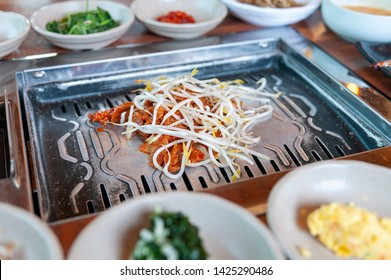 Grilled marinated pork kimchi topped with bean sprout eaten with various side dishes of vegetable and seasoning sauces at a traditional Korean cuisine restaurant in Korea