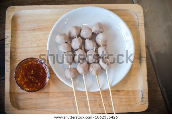 grilled meat ball with chilly saucec and cucumber put on the white dish with on wood table