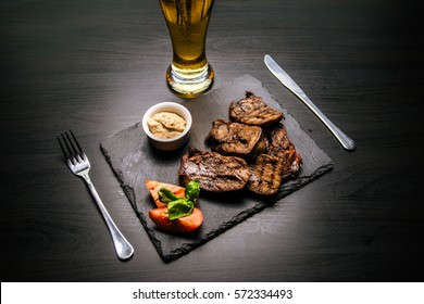 grilled meat and beer on black background