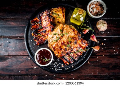 Grilled meat concept. bbq pork ribs with barbeque sauce, olive oil. fresh herbs on dark wooden background copy space