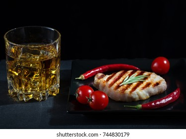 Grilled meat with garnish and a glass of whiskey. Dark background. The concept of traditional food.