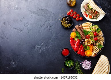 Grilled meat kebabs, vegetables on a black plate with tortillas, flat bread. Slate stone background. Copy space. Top view.