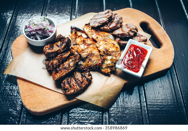 Grilled meat mix on the wooden plate.