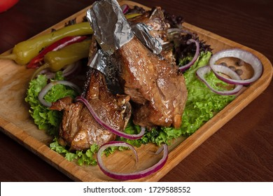 grilled meat on the bone with greens and vegetables. BBQ menu