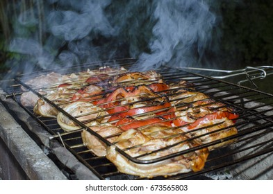 Grilled meat on the grill with smoke