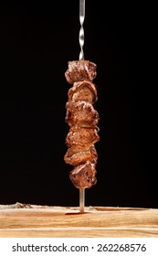 Grilled meat on skewer on black background with logs