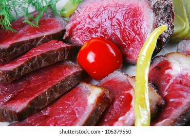 grilled meat on white plates with peppers and tomato