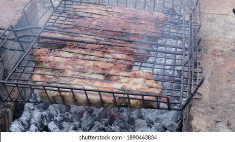 grilled meat on a wire rack and charcoal