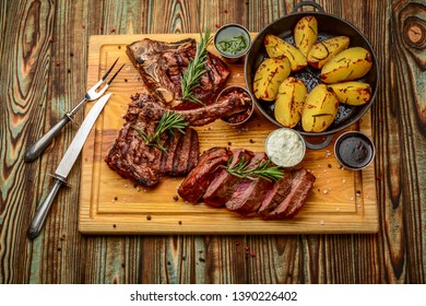 Grilled meat, porkchop with potatoes in pan. Grilled meat, potatoes, frying pan