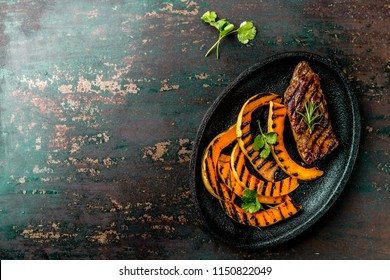 Grilled meat and pumpkin on black plate. Autumn menu. Top view.