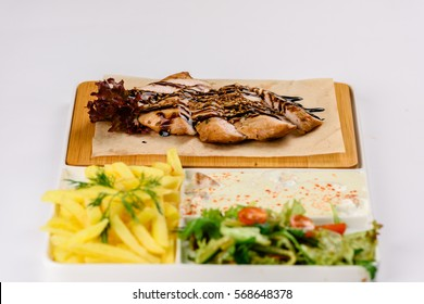 Grilled meat with sauce, salad and French fries on white background
