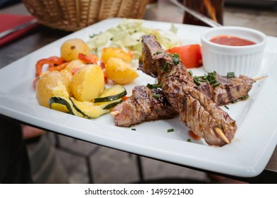 Grilled meat skewers served with baked potatoes and hot chili sauce served as a traditional dish of French cuisine in the restaurant of Carcassonne, France