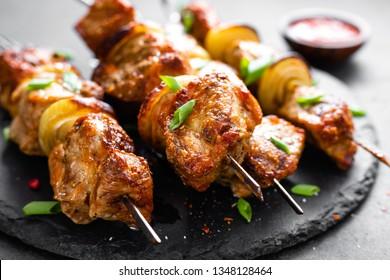 Grilled meat skewers, shish kebab on black background