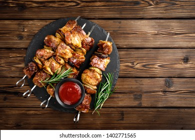 Grilled meat skewers, shish kebab on wooden background, top view
