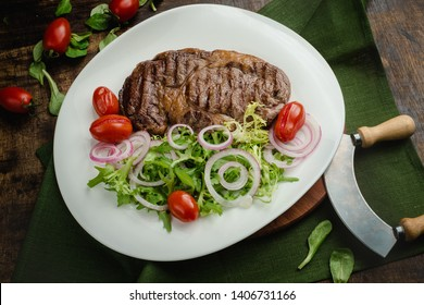 Grilled meat steak with arugula, sweet onion rings and cherry tomatoes. Cafe menu on a wooden background in warm colors with copy space.