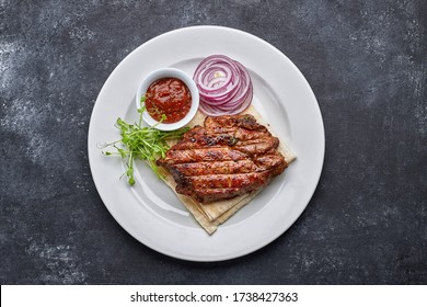 Grilled meat steak with onions, sauce and microgreen, on pita bread, on a white plate, against a dark background. space for text. top view