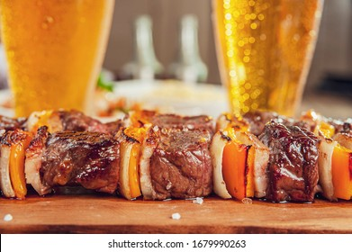 Grilled meat stick on a cutting board with beers - 180º angle (Espetinho de carne)