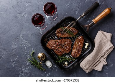 Grilled meat Top Blade steaks on frying pan and red wine on dark background
