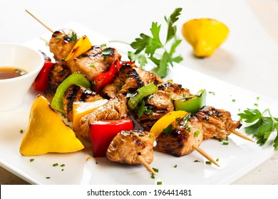 Grilled meat and vegetable kebabs on the white plate