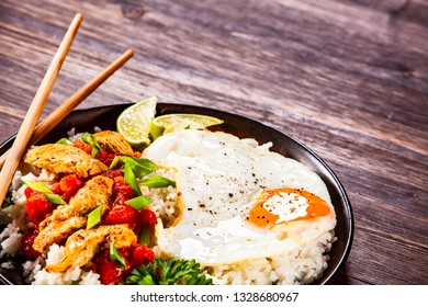 Grilled meat, white rice,fried egg vegetables on wooden table
