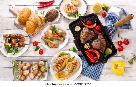 Grilled meats with vegetables on white wooden table. Top view