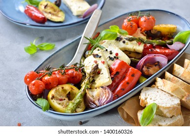 Grilled mediterranean vegetables with warm feta cheese served on a blue ceramic plate on a table with concrete look