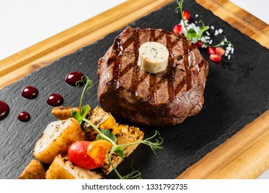 grilled Medium rare barbecue steak Ribeye with herb butter on cutting board