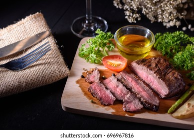 Grilled Medium Rare Steak with red wine, herbs and spices on wooden table.(Selective Focus.)