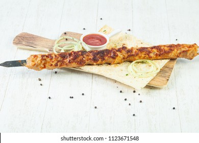 Grilled minced chicken kebab with sauce and onion