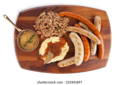Grilled Mixed sausage served with infuse red cabbage mashed potato with gravy and mustard sauce, isolated on white.