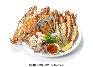 Grilled Mixed Seafood Contain Blue Crabs, Mussels, Big Prawns, Calamari Squids and Roasted Barracuda Fish Garlic with Spicy Chili Sauce and Lemon on Platter, Isolated on White Background with Shadow.