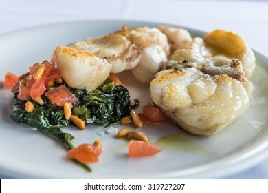 Grilled monkfish garnished spinach with cedar nut and tomatoes
