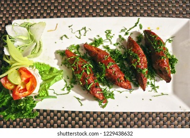 Grilled mutton/meat seek kabab(Indian kashmiri dish) with salads &  small green leaves toppings.
