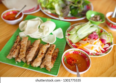 Grilled Nem (Vietnamese food) - Grilled mashed pork skewers with side dishes and chilli sauce