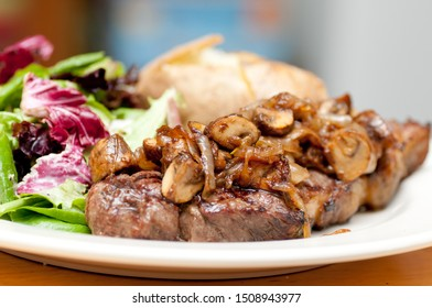 grilled new york strip steak with salad and baked potato