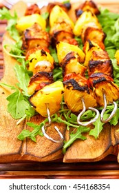 Grilled Norwegian Salmon Skewers with vegetables, pineapples, cheese and fresh tomato on the ruccola  close-up on the olive wooden tales and table. BBQ picnic, family dinner, healthy food
